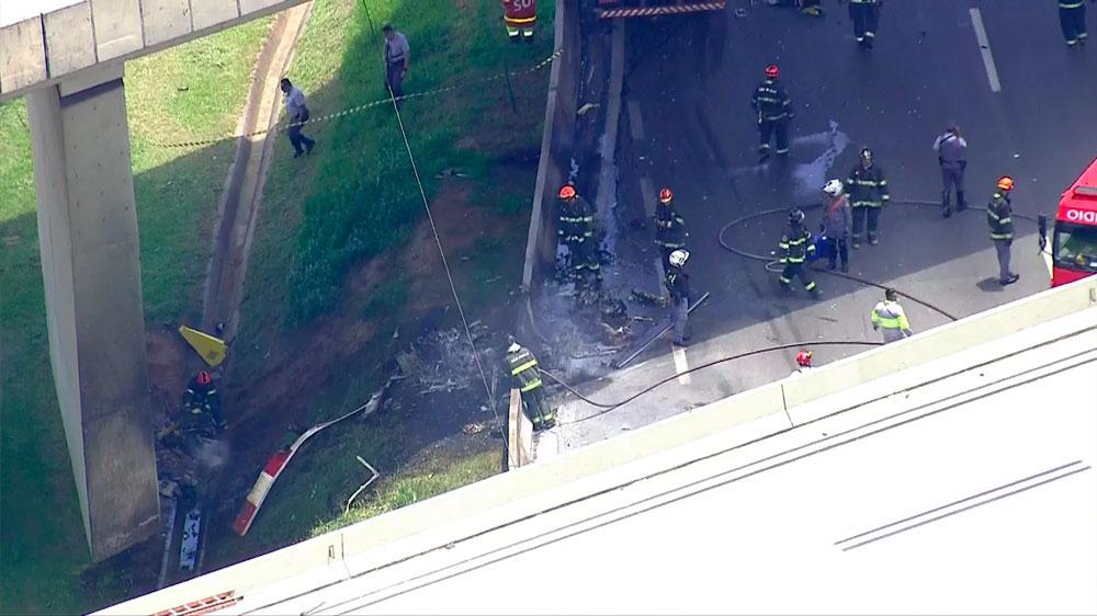 Bombeiros observam o que sobrou do helicóptero. Foto: TV Globo/Reprodução